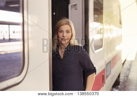 Young blonde woman getting on the train