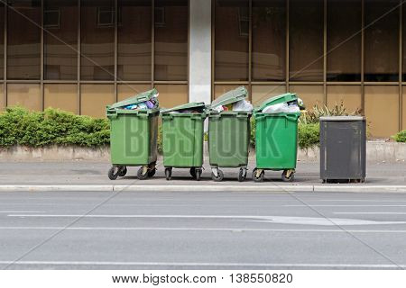 Group of over filled Wheelie bins, waste containers with wheel in green color full of trash on footpath in Adelaide, South Australia
