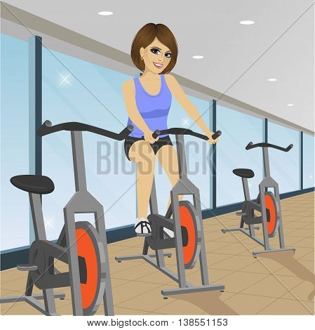 young woman doing indoor biking exercise at the gym