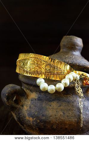 Clay pot full of jewelry on dark wooden background. Copy space