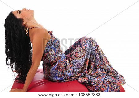 Sexy brunette in summer dress reclining on footstool