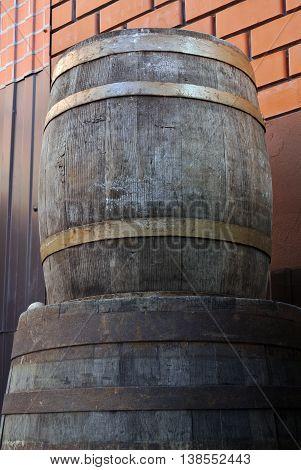 Old oak wine barrels on background of red brick wall