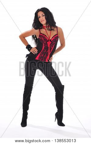 Sexy brunette in a red corset and high boots posing