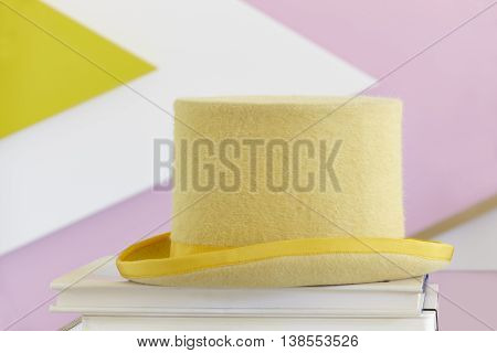 Yellow top hat still life with books and painted wall. Fancy party
