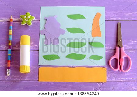 Hippo, leaves, palm tree trunk cut from colored paper. Set for children craft projects. Paper card hippo craft. Glue stick, scissors, pencil, eraser on wooden background. Top view