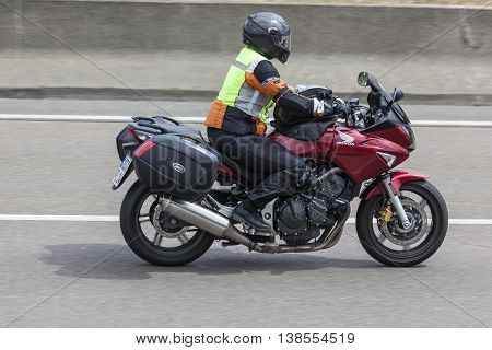 FRANKFURT GERMANY - JULY 12 2016: Motorcyclist on a Honda GIVI motorcycle driving on the highway in Germany