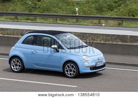 FRANKFURT GERMANY - JULY 12 2016: Blue Fiat 500 driving on the highway in Germany
