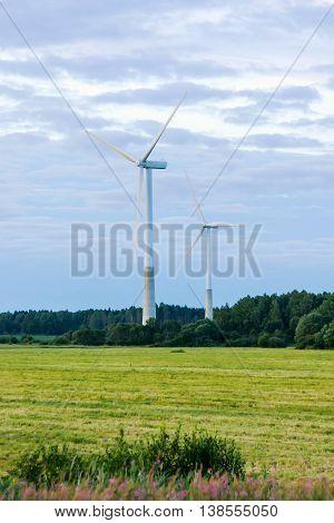 Windmill on rural field in the sunset. Wind turbines farm.