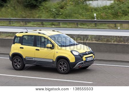 FRANKFURT GERMANY - JULY 12 2016: Yellow Fiat Panda Cross SUV driving on the highway in Germany