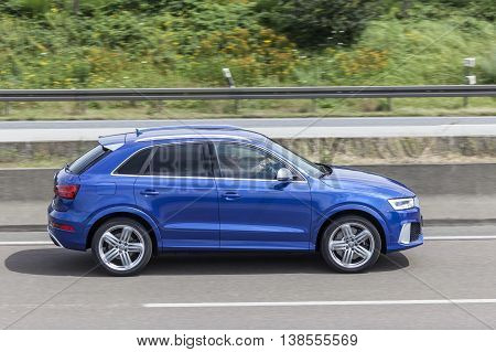 FRANKFURT GERMANY - JULY 12 2016: Blue AUDI Q3 luxury SUV driving on the highway in Germany