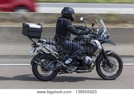 FRANKFURT GERMANY - JULY 12 2016: Motorcyclist on the BMW R1200 GS motorcycle driving on the highway in Germany