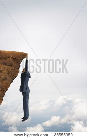 business challenge concept businessman clinging on to a cliff