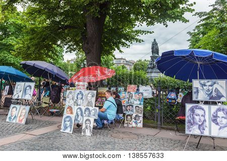 SAINT PETERSBURG, RUSSIA -JULY 09, 2016: Artists in the center of St. Petersburg on Nevsky Prospect paint portraits,  in the background a monument to Catherine the Great