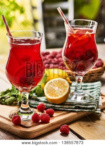 On wooden boards are ice cold beverage couple glasses with red raspberry lemon cocktail . Alcohol country cocktail beverage number hundred eighty with checkered napkin. Outdoor country cocktail .