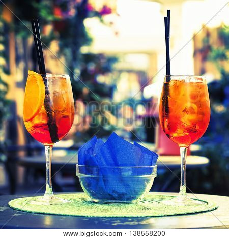 Aperol Spritz Cocktail. Alcoholic beverage on table with ice cubes and oranges.