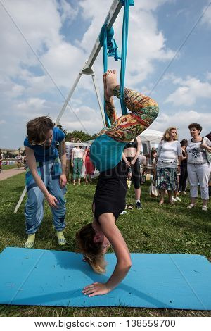 Saint-Petersburg Russia - June 26 2016: Celebration of the World Day of Yoga. Girl - indicates to everyone how to properly perform yoga asana aero in hammocks.