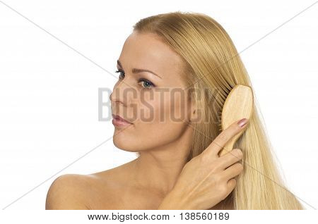 Beautiful young woman combing her hair on white background
