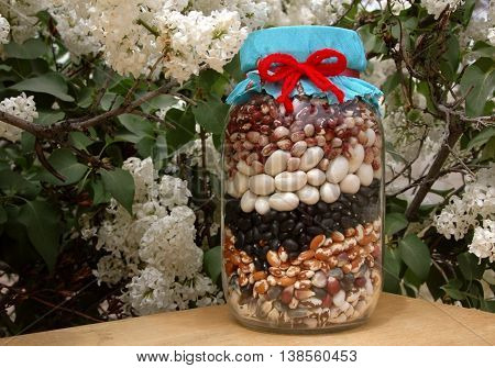 Seed corn and beans in a jar, with springtime flowers.