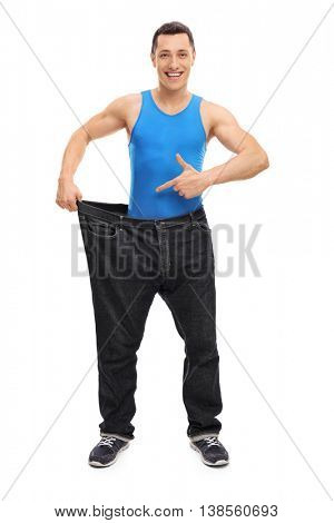 Full length portrait of a handsome man showing his old pair of oversized jeans isolated on white background
