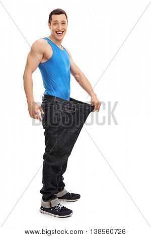 Full length portrait of a joyful guy in an oversized pair of jeans isolated on white background