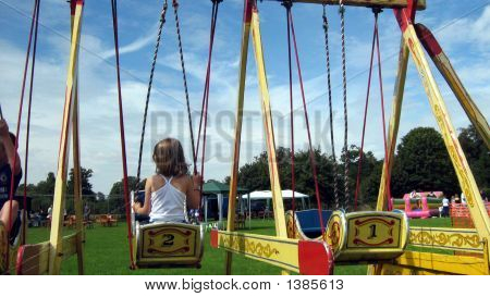 Girl/Children Playing On Swing Boats. A Fete/Show