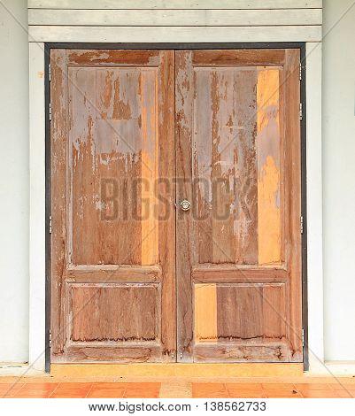 Old broken wooden door brown color with white wall