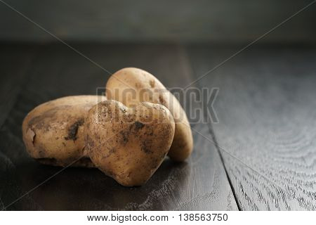 heart shaped potatoes on black oak table, shallow focus