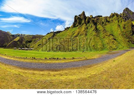The photo was taken Fisheye lens. Camping in the canyon Pakgil, Iceland. The canyon -  green grass and moss on fantastic rocks. On canyon there is dirt road