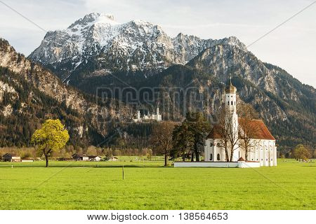St. Coloman Church in Southern Germany in back famous Neuschwanstein Castle in spring time
