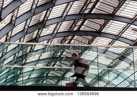 London, UK - July 5, 2016 - A traveller passing in motion along the elevated walkway at Kings Cross train station.