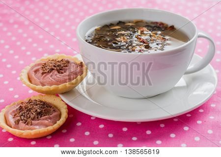 Cup Of Tea And A Tartlet With Cream On A Pink Background
