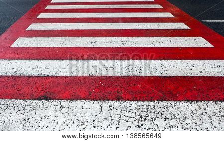 Red and white pedestrian crossing on road
