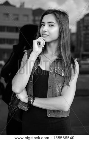 Beautiful sexy young brunette woman with long wavy hair thin slim figure perfect body and beautiful face make-up, wearing a black suit and vintage denim jacket. summer accessory, black backpack