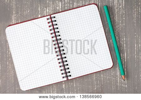 Top view of spiral notebook and pencil on the grey wooden background.
