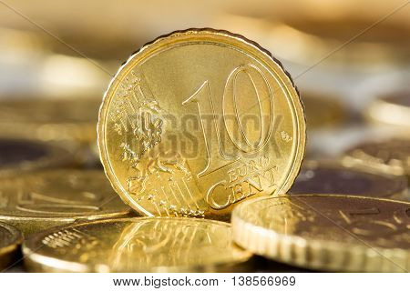 Closeup of a 10 euro cent coin standing between other coins