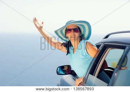 Relaxed happy woman on summer roadtrip travel vacation leaning out car window on sea and blue sky background.