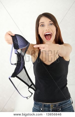 Angry woman with bra in hand. Betrayal concept