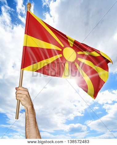 Person's hand holding the Macedonian national flag and waving it in the sky, 3D rendering