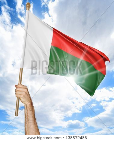 Person's hand holding the Madagascan national flag and waving it in the sky, 3D rendering