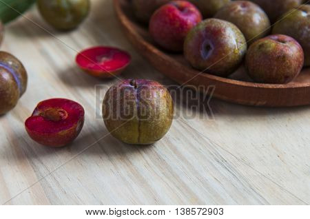 Delicious plums on the old wooden background, selective focus