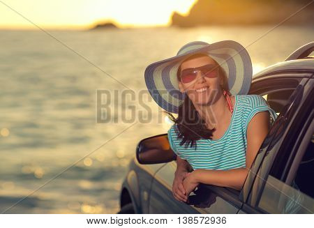 Relaxed happy woman on summer roadtrip travel vacation leaning out car window on sea and blue sky background sunlight