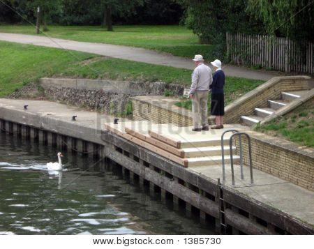 Elderly Couple Standing Beside The Lake