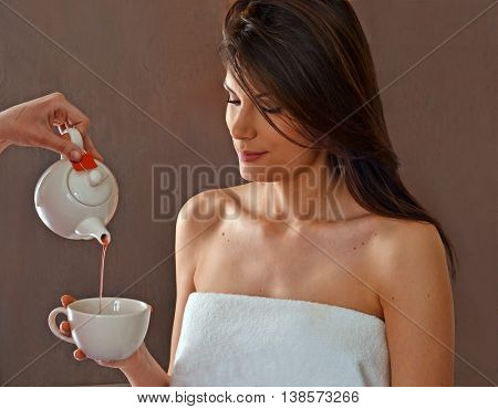 Drinking tea after beauty body treatment at spa center.