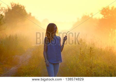 Morning walk. Girl in the field. Summer holiday. Early awakening.Photo toned in retro.