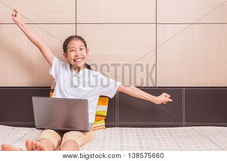 Happy smiling and excited asian girl using notebook computer to study on her bed reaching out her arms in excited and successful pose room for copy space text