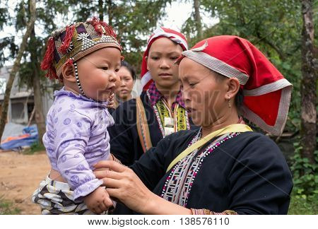SAPA, VIETNAM, February 12, 2016 the mother and baby ethnic Dao, highland Sa Pa, Vietnam, in traditional costume playing traditional New Year's Day
