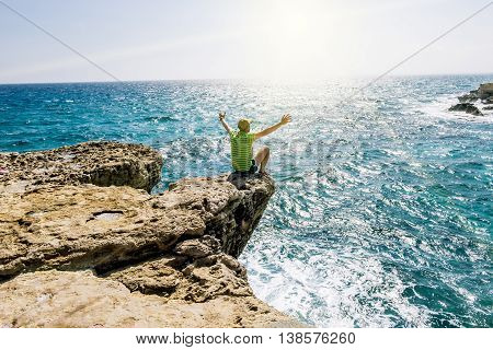 25 may 2016.Cape Greco.A man sits on a ledge of rock above the sea at Cape Greco . Cyprus.