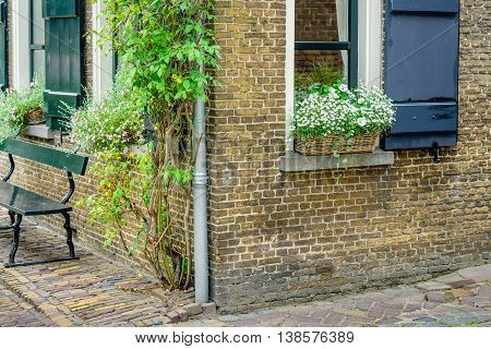 Closeup of the corner of an old house in a small historic village in the Netherlands with flowering plants in a basket on the window sill.