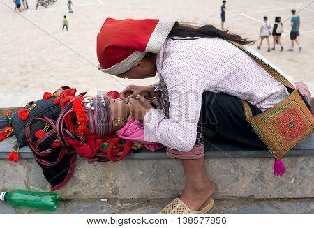 SAPA. VIET NAM, February 12, 2016 mother, ethnic Dao, high mountains, Sapa, Vietnam. Children eat