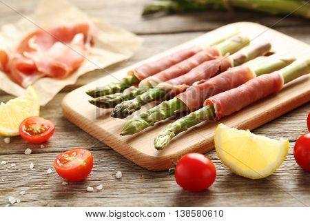 Fresh Green Asparagus Wrapped In Jamon On A Grey Wooden Table